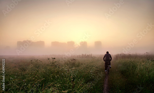 Fototapeta postać jadąca rowerem do miasta obraz