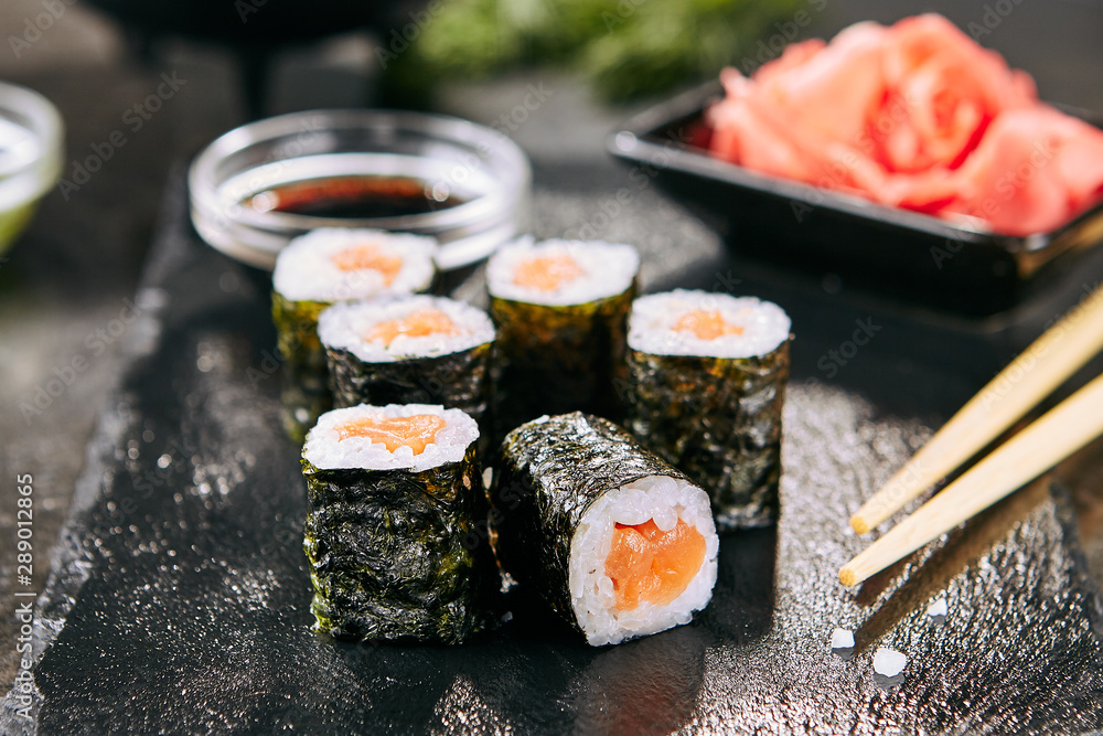 Fototapety, obrazy: Macro shot of salmon hosomaki sushi on natural black slate plate background with selective focus. Thin maki sushi rolls with raw trout, cucumber, rice, sesame and nori closeup
