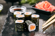 Macro shot of salmon hosomaki sushi on natural black slate plate background with selective focus. Thin maki sushi rolls with raw trout, cucumber, rice, sesame and nori closeup