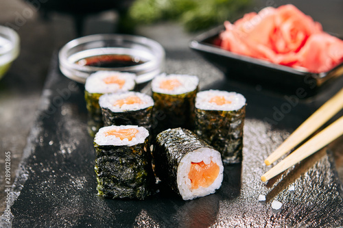 Fototapeta Macro shot of salmon hosomaki sushi on natural black slate plate background with selective focus. Thin maki sushi rolls with raw trout, cucumber, rice, sesame and nori closeup obraz