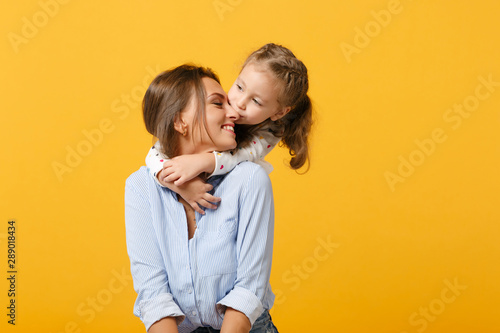 Obraz Woman in light clothes have fun with cute child baby girl 4-5 years old. Mommy little kid daughter isolated on yellow background studio portrait. Mother's Day love family parenthood childhood concept. - fototapety do salonu