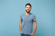 Young smiling handsome man in casual clothes posing isolated on blue wall background, studio portrait. People sincere emotions lifestyle concept. Mock up copy space. Holding hands in pockets.