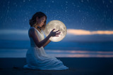 Delicate photography, Astrology, Women's magic. Beautiful attractive girl on a night beach with sand and stars hugs the moon, art photography.