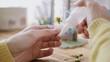 Woman gluing miniature handmade flower