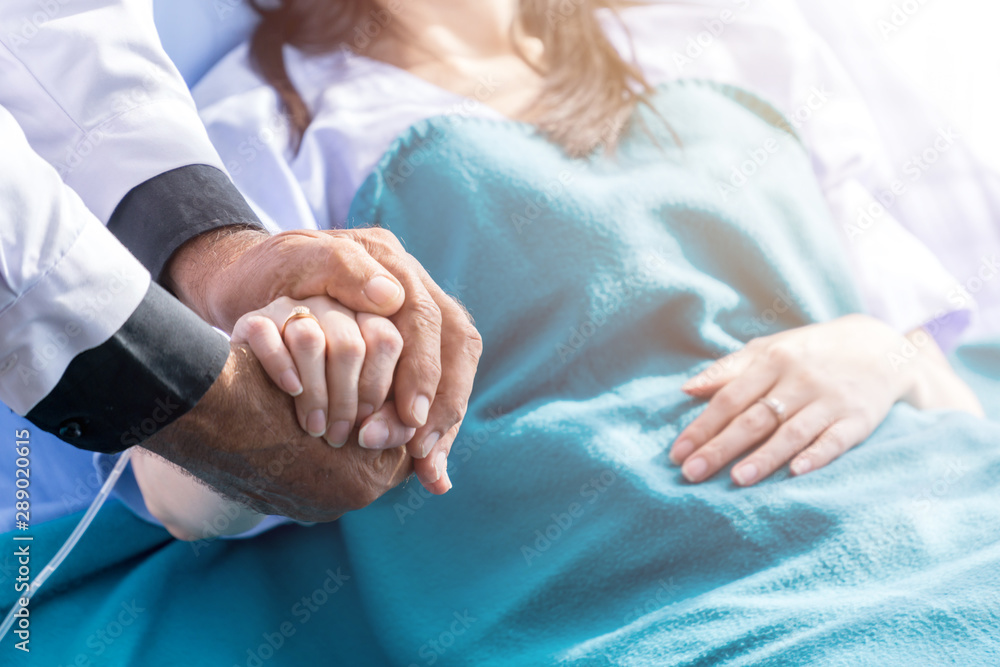 Fotografia Male doctor holding female patient hand on the hospital bed.
