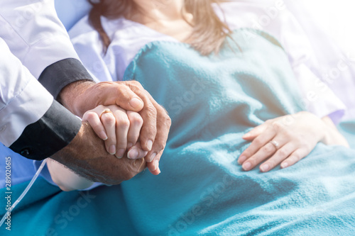 Male doctor holding female patient hand on the hospital bed. Poster Mural XXL