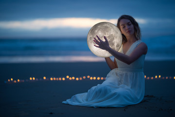 Gentle image of a girl, Astrology, Female magic. Beautiful attractive girl on a night beach with sand hugs the moon, art photography