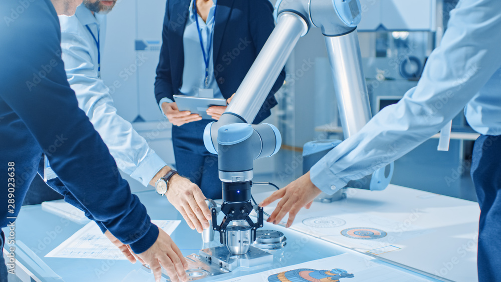 Fototapety, obrazy: Team of Industrial Robotics Engineers Gathered Around Table With Robot Arm, They Use Tablet Computer to Manipulate and Program it to Pick Up and Move Metal Component. Focus on Hands