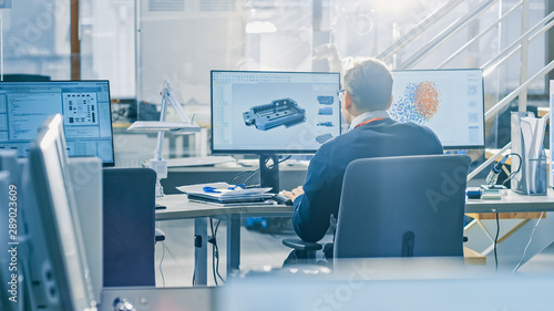 Aluminium Prints Equestrian Back View of Industrial Engineer Working on Desktop Computer in Bright Office. Screens Show IDE / CAD Software, Implementation of Machine Learning, Neural Networking and Cloud Computing