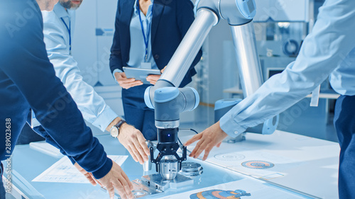 Team of Industrial Robotics Engineers Gathered Around Table With Robot Arm, They Use Tablet Computer to Manipulate and Program it to Pick Up and Move Metal Component. Focus on Hands - 289023638