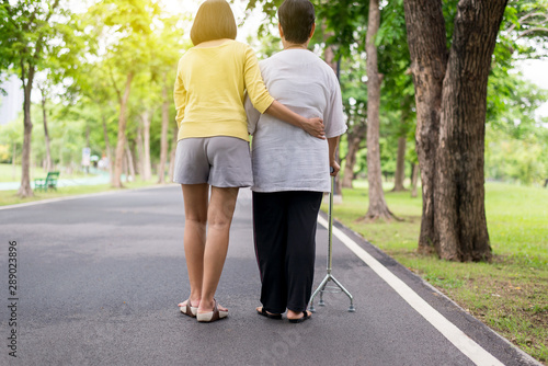 Elderly Asian female walking to do physical with stick at park,Daughter take care and support