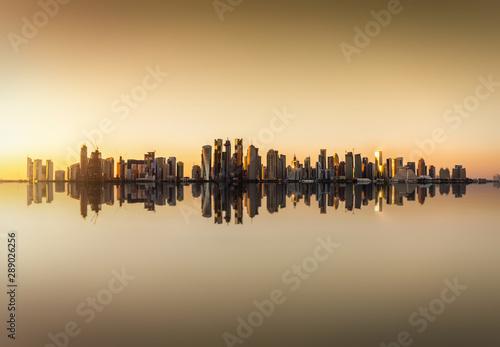 Photo Die Skyline von Doha in Katar bei Sonnenuntergang  mit Reflektionen im Wasser
