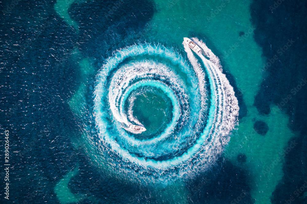 Fototapeta Zwei Motorboote formen einen Kreis aus Luftblasen und Wellen auf dem türkisem Meer