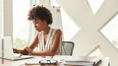 Business expert. Beautiful afro american woman working with laptop while sitting in the modern office