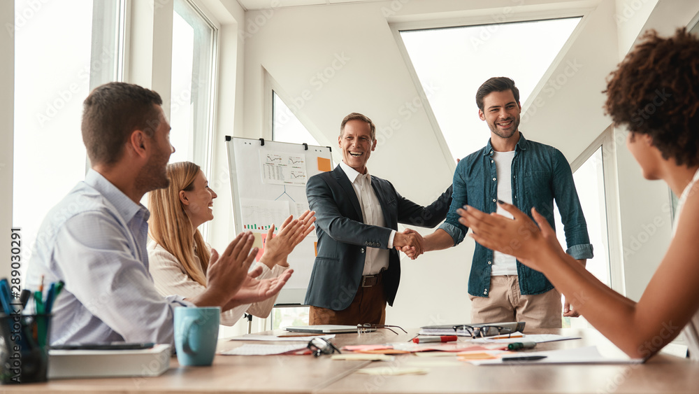 Fototapety, obrazy: Good job Two cheerful colleagues shaking hands and smiling while having a meeting in the modern office