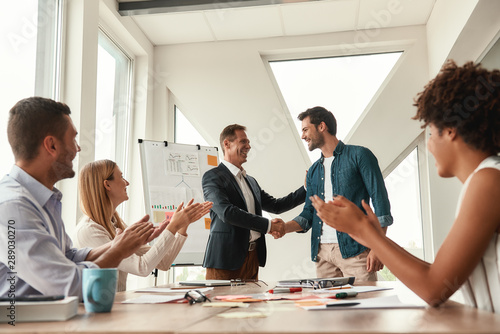 Fototapety, obrazy: Welcome to our team Two cheerful colleagues shaking hands and smiling while having a meeting in the modern office