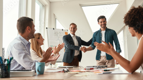 Good job Two cheerful colleagues shaking hands and smiling while having a meetin Wallpaper Mural