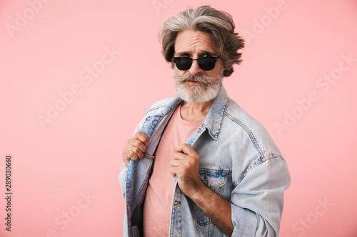 Fotografia  Portrait of fashion old man with gray beard wearing sunglasses and denim jacket