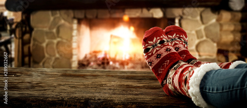 Foto auf AluDibond Logo Woman legs with christmas socks and fireplace