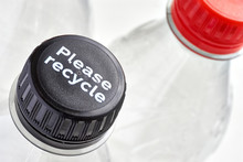 Plastic Bottles And Black And Red Bottle Caps With Please Recycle Message Against A White Background. Concept Of Plastic Pollution.