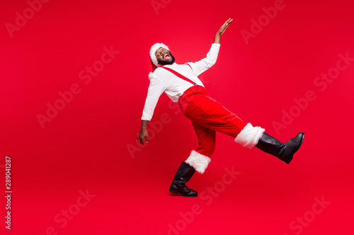 Full size profile side photo of cheerful black santa claus going moving laughing wearing white pullover pants trousers isolated over red background