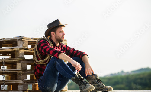 Watching sunset. Farmer cowboy handsome man relaxing after hard working day at ranch. Romanticism of western culture. Farmer in hat sit relax. Farmer enjoy view from his farm. Peaceful mood
