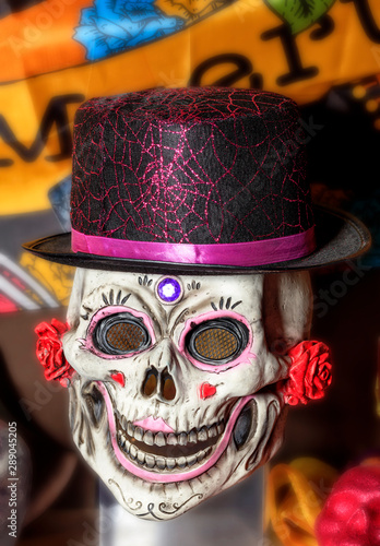 Valokuva  Halloween, skull doll with female makeup and a black-red hat, isolated on a blurred background