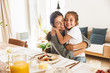 canvas print picture - Image of happy family mother and little daughter hugging while having breakfast at home in morning