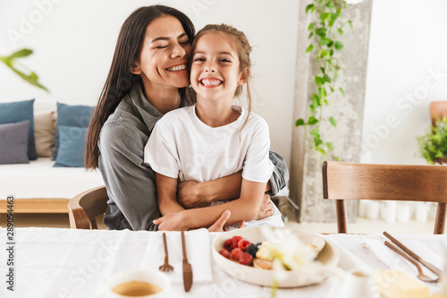 Fototapeta Image of attractive family mother and little daughter hugging while having breakfast at home in morning obraz