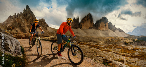 Couple cycling on electric bike, rides mountain trail. Woman and Man riding on bikes in Dolomites mountains landscape. Cycling e-mtb enduro trail track. Outdoor sport activity.
