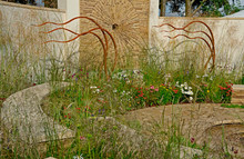 A Enclosed Modern Garden Designed To Show The Role Of Wind And Water Through Circular Planting And Sculpture