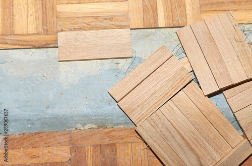 Fototapeta Renovation of a damaged parquet while fixing new wooden tiles instead of old obraz na płótnie