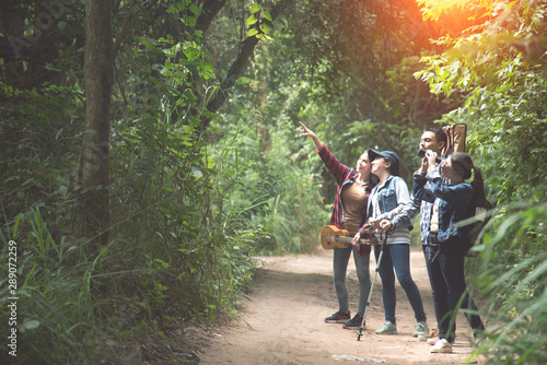 Fotografiet  Friends or tourists with colorful backpacks in forest