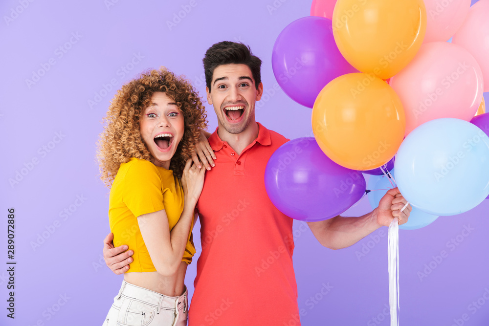 Fototapeta Cheerful young couple standing isolated over violet