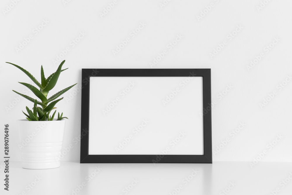 Black frame mockup with a aloe vera in a pot on a white table.Landscape orientation.
