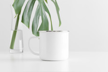 Enamel Mug Mockup With A Monstera Leaf In A Glass Vase On A White Table.