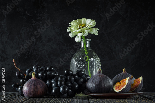 Fototapeta ripe whole and sliced figs with a bunch of black grapes and one flower in an empty decanter on old wooden boards against the background of a black textured concrete wall. elegant still life side view obraz