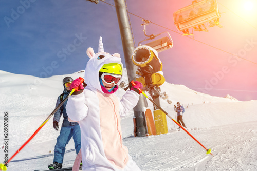 Cuadros en Lienzo Cute adorable preschooler caucasian kid girl portrait with ski in helmet, goggles and unicorn fun costume enjoy winter sport activities