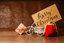 Decoration For Christmas. Gift, Postcard And Toy Bicycle On A Brown Wooden Background. Concept Of Holidays And New Year