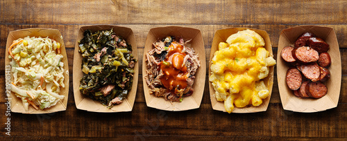 Fototapeta assorted trays of texas bbq with collard greens, hotlinks, pulled pork, mac and cheese, coleslaw obraz