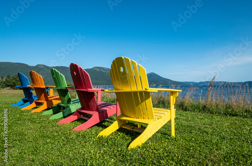 A Row of Bright and Colorful Adirondack Chairs Facing Bonne Bay on a Sunny Day i Canvas Print