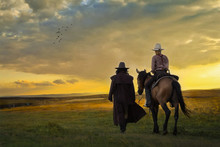 The Silhouette Of Two Cowboys, Who Were Traveling With His Horse