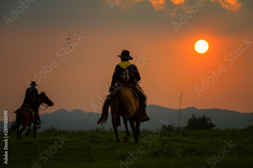 Fototapeta The silhouette of two cowboys, who were traveling with his horse obraz