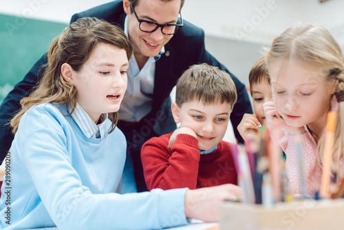 fototapeta na szkło Gruppenarbeit in der Schule und alle Schüler arbeiten gemeinsam