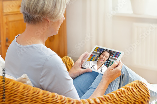 Obraz telemedicine concept, old woman with tablet pc during an online consultation with her doctor in her living room - fototapety do salonu