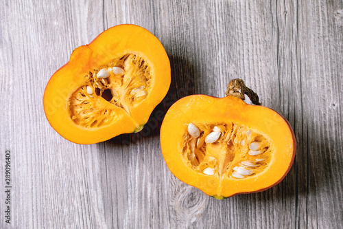 fototapeta na drzwi i meble Two halves of raw organic hokkaido pumpkin with seeds over grey wooden background. Flat lay, space