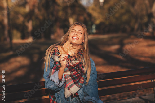 Portrait of a beautiful blonde with a smile on face holding a leaf in hand in the park