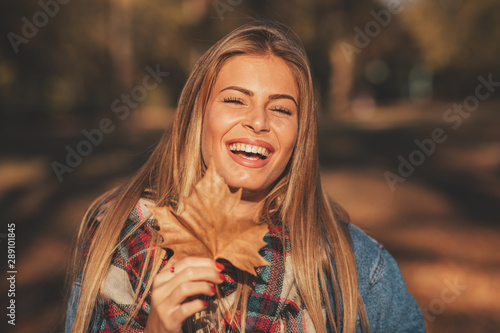 Fotografie, Obraz  Portrait of a beautiful blonde with a smile on face holding a leaf in hand in th