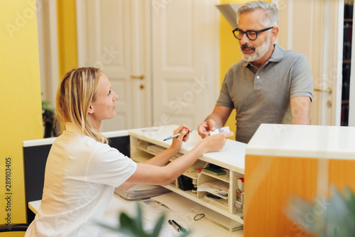 Patient settling up with a receptionist Fototapet