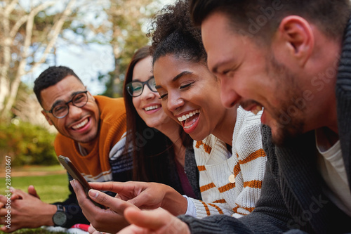 Obraz group of multi ethnic friends in college lying together in the park enjoying watching text or video on mobile phone - smiling group of students - fototapety do salonu